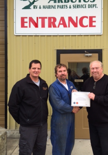 Michael Lewinsky receives his Certificate from Hubert Sester, Port Alberni Branch Manager. Dwayne Kuemper, Arbutus RV Service Director (left).