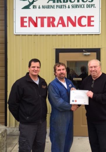 Michael Lewinsky receives his Certificate from Hubert Sester, Port Alberni Branch Manager. Dwayne Kuemper, Arbutus RV Service Director (left).